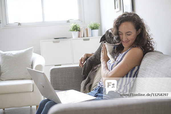Young woman with laptop cuddling with her dog on sofa