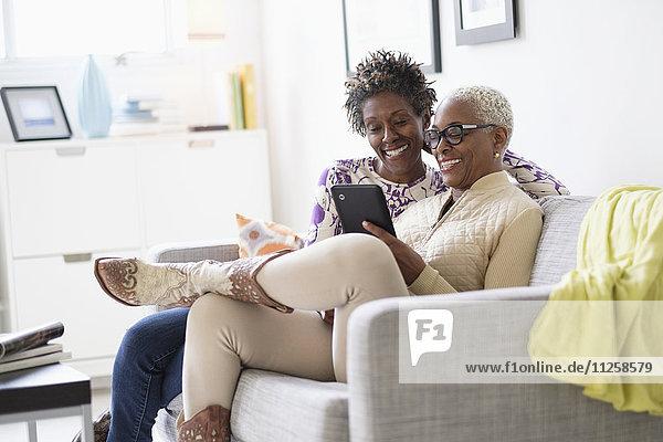 Smiling women using tablet in living room