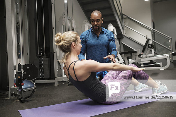 Woman exercising with personal trainer in gym