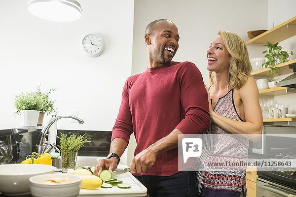 Couple preparing dinner in kitchen and laughing