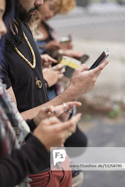 Young people standing in row using smartphones