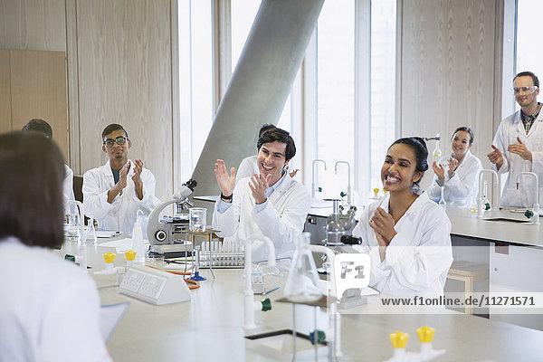 Studenten klatschen für ihren Klassenkameraden im Klassenzimmer des Wissenschaftslabors