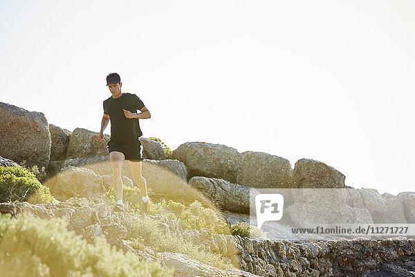 Männlicher Triathlet auf sonnigem Felsweg