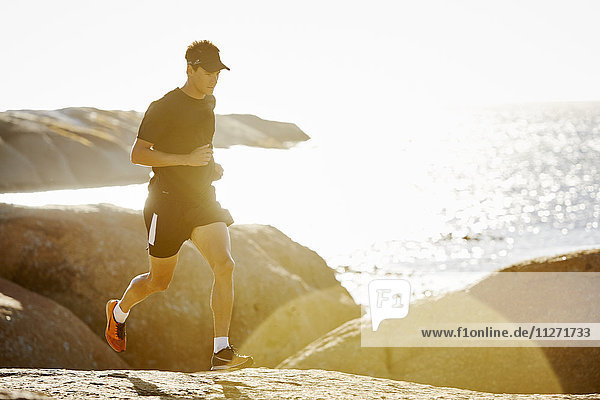 Männlicher Triathlet auf felsigem Trail entlang des sonnigen Ozeans