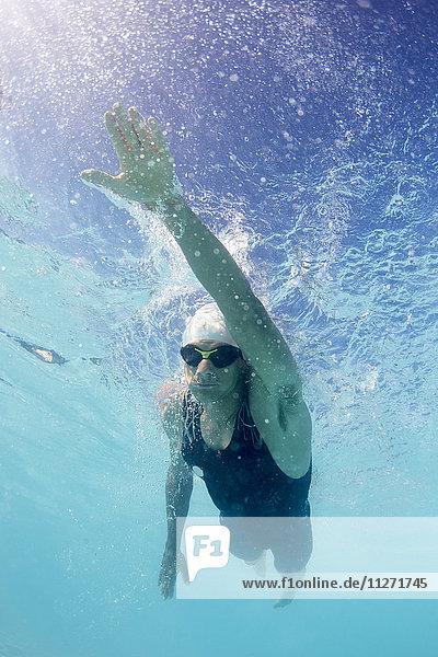 Männlicher Schwimmer,  der im Schwimmbad unter Wasser schwimmt.