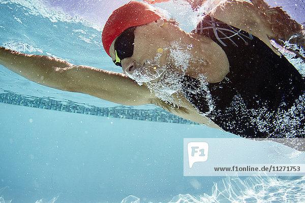 Männlicher Schwimmer  der im Schwimmbad unter Wasser schwimmt.