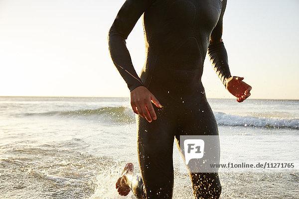 Triathletenschwimmer im Neoprenanzug  der aus der Brandung läuft