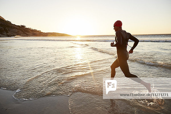 Triathletenschwimmer im Neoprenanzug  der bei Sonnenaufgang in die Brandung läuft.