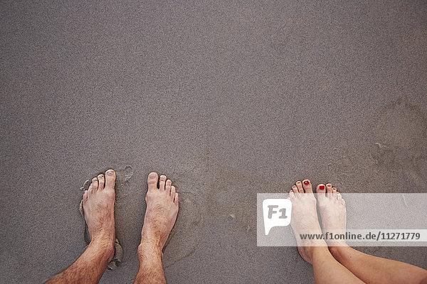 Persönliche Perspektive Barfuß-Paar im nassen Sand am Strand stehend