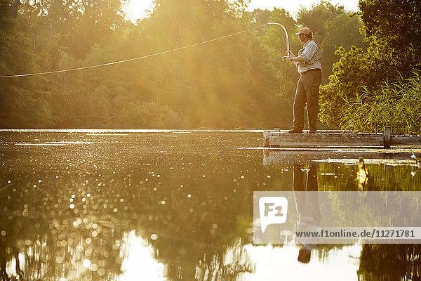 Senior Mann Fliegenfischen am Dock des Sommersees