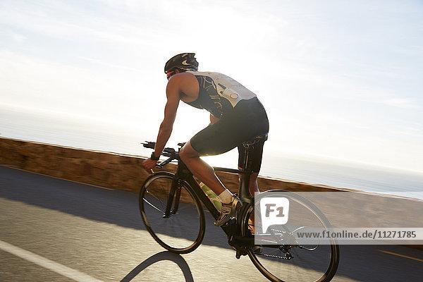 Männlicher Triathlet Radfahrer auf sonniger Seestraße