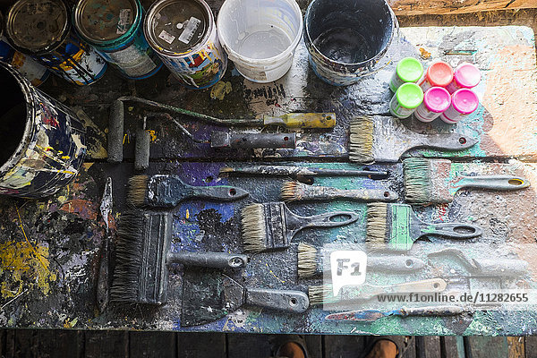 Used paintbrushes and paint cans on table