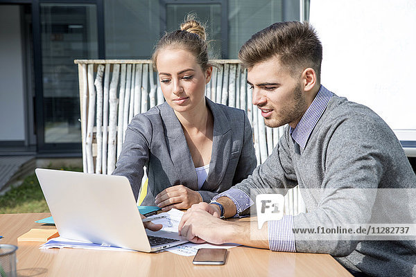 Two business people working on laptop together