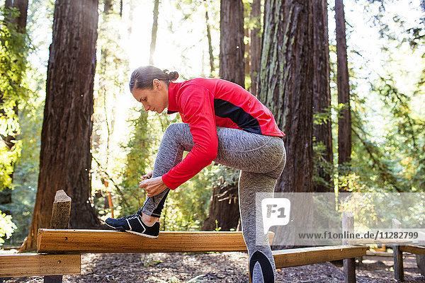 Woman tying shoelace on forest path
