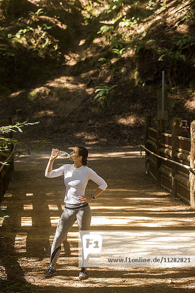 Woman drinking water on sunny forest path