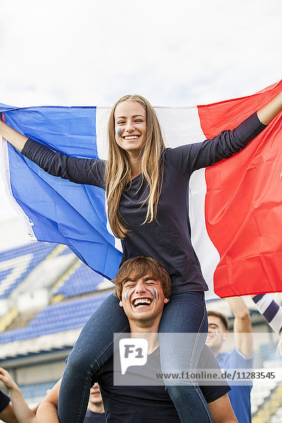 Young woman with French flag celebrating