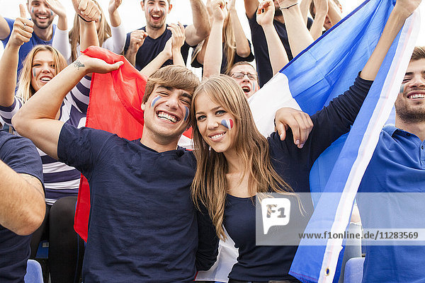 Group of soccer fans celebrating with French flag