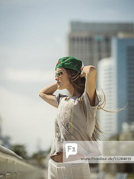 Caucasian woman wearing baseball cap and sunglasses in wind