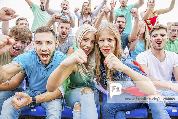 Group of soccer fans in stadium cheering and shouting