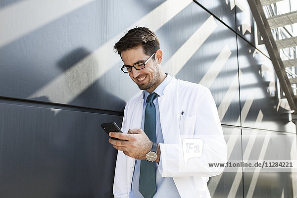 Doctor with eyeglasses receiving message on smartphone