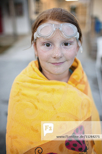 Portrait of Caucasian girl wrapped in towel after swimming