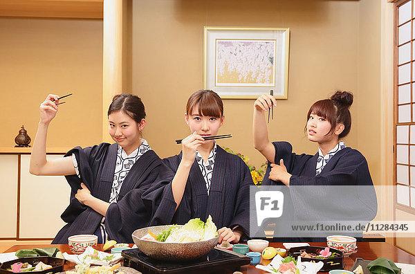 Young Japanese women wearing yukata eating at traditional ryokan inn