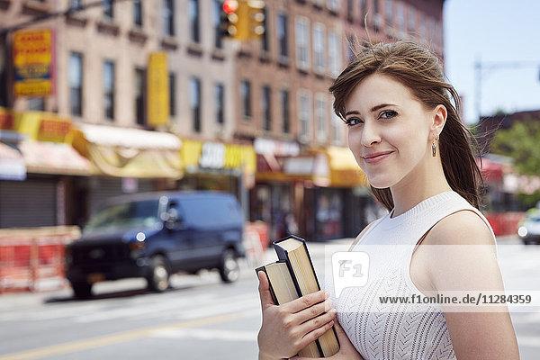 Caucasian woman carrying books on city sidewalk