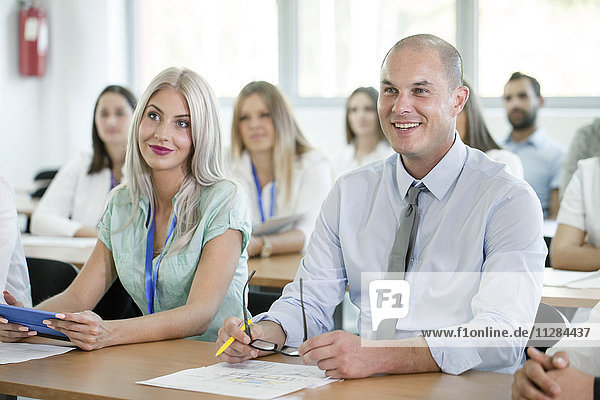 Business people in training class listening to speaker