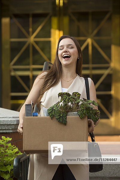 Laughing Caucasian carrying box with potted plant
