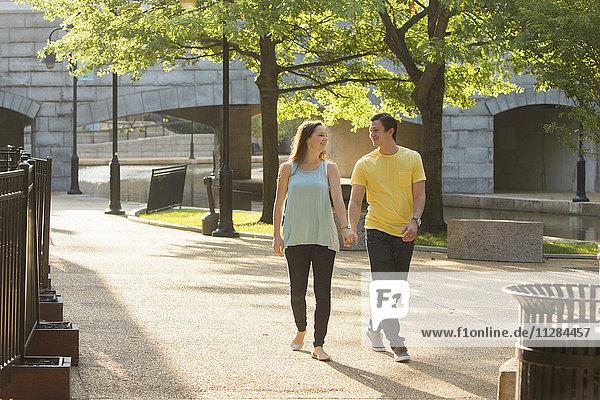 Caucasian couple walking in park