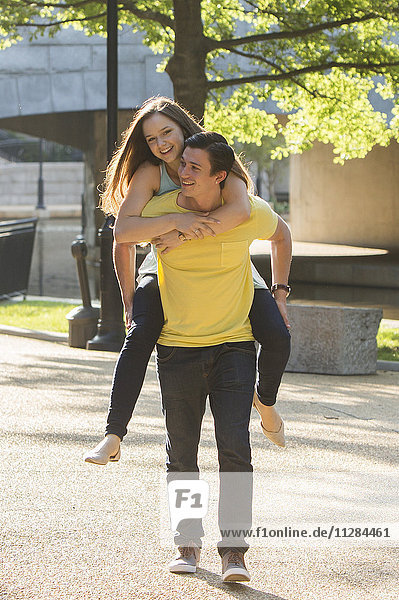 Caucasian man carrying girlfriend piggyback in park
