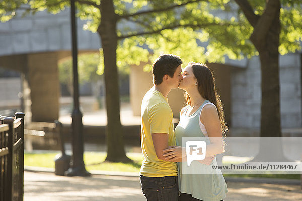 Caucasian couple kissing in park