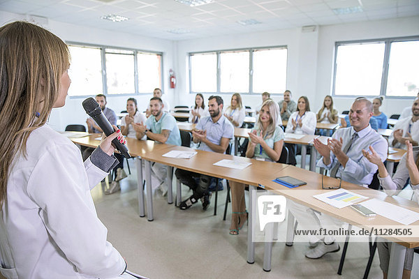 Audience clapping for speaker in training class
