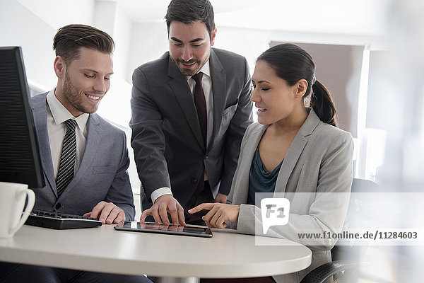 Business people talking in office using digital tablet and computer