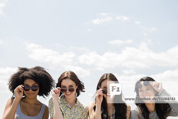 Portrait of smiling women holding sunglasses outdoors