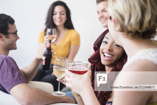 Smiling friends drinking at party