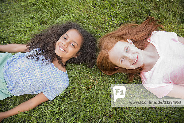 Portrait of smiling girls laying in grass