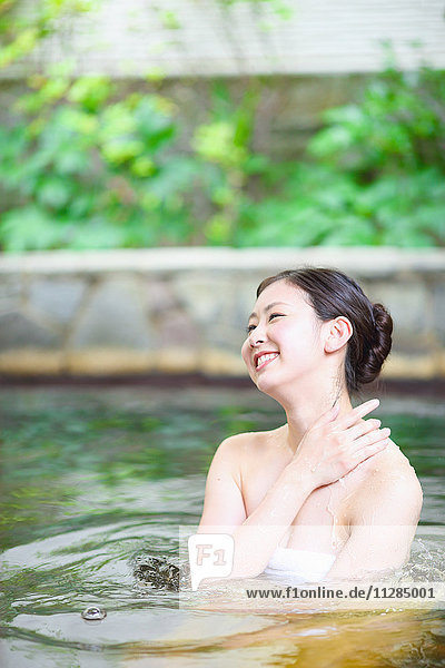 Young Japanese woman bathing at traditional onsen hot spring