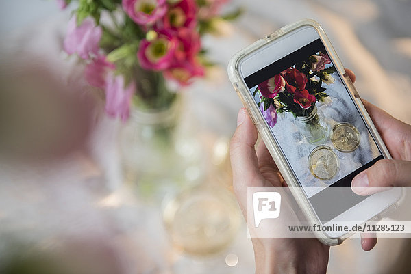 Caucasian woman photographing champagne and flowers with cell phone