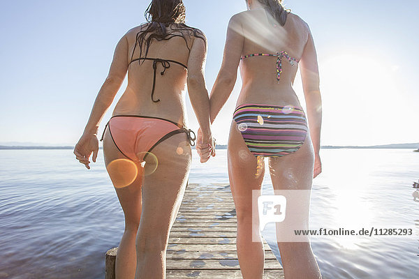 Two young women walk on pier holding hands