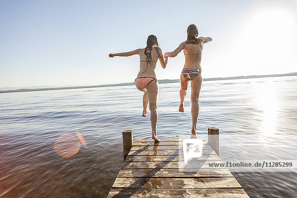 Two young women jumping into lake