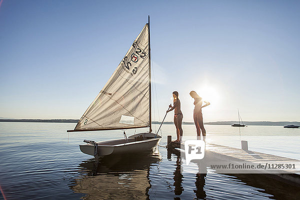 Two young women standing by sailboat