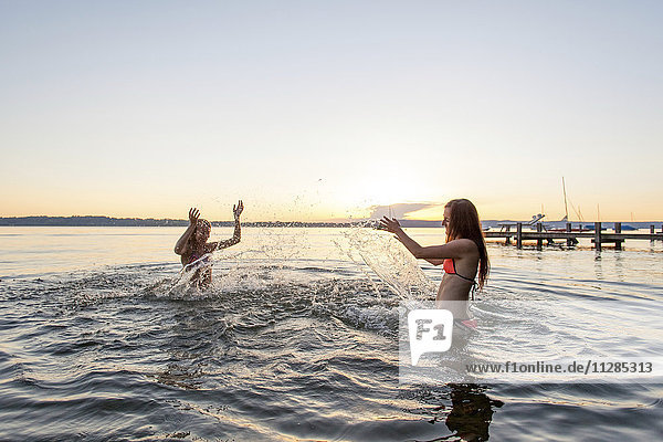 Two young women splashing each other in lake