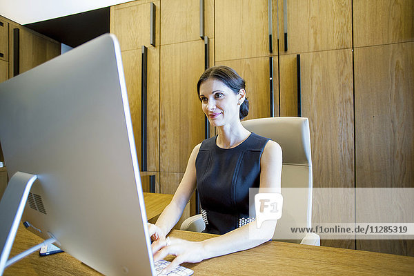 Businesswoman in lobby working on computer