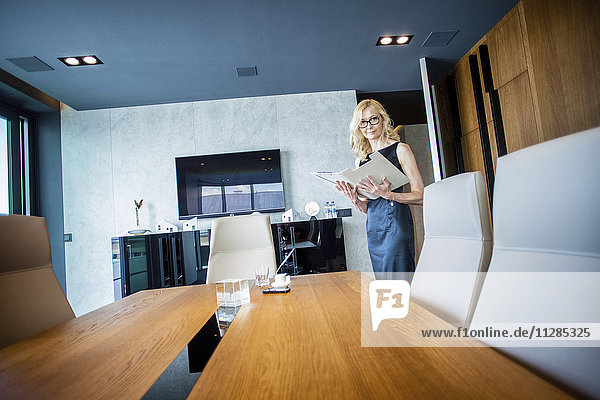 Businesswoman holding documents in board room