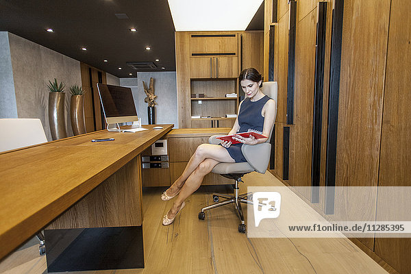 Businesswoman in mini dress sits at reception desk