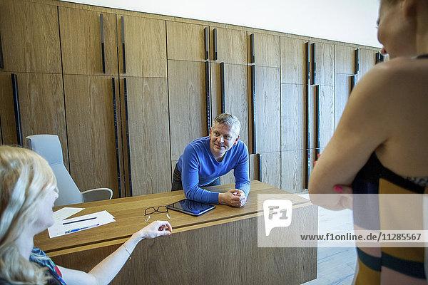 Male receptionist at desk talking to businesswomen