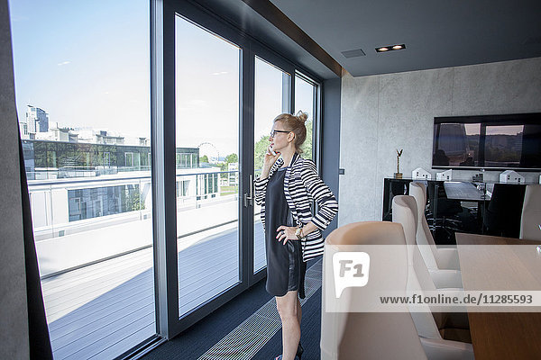 Businesswoman in office looking through window