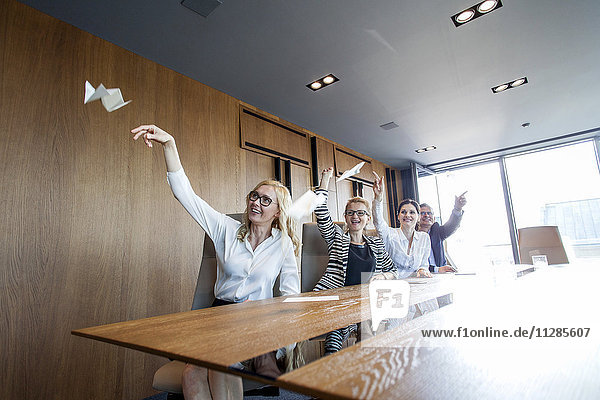 Business people in board room throwing paper airplanes
