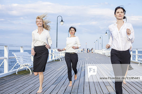 Group of businesswomen running along jetty